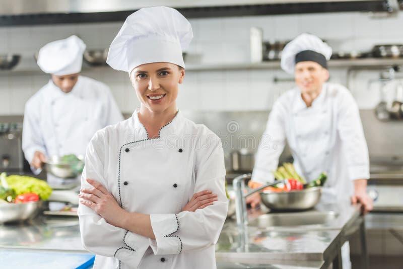 uśmiechnięta szef kuchni pozycja z krzyżować rękami i patrzeć kamerę obrazy royalty free