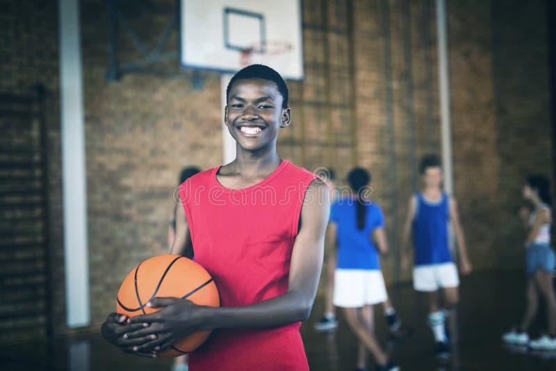 Uśmiechnięta szkolna chłopiec trzyma koszykówkę podczas gdy drużynowy bawić się w tle obrazy royalty free