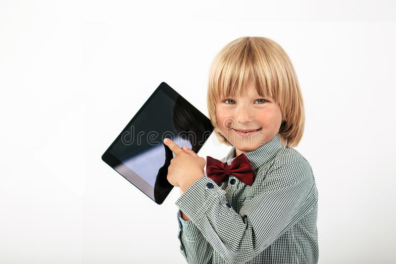 Uśmiechnięta Szkolna chłopiec w koszula z czerwonym łęku krawatem, trzymający pastylka komputer i zieleni jabłka w białym tle obrazy royalty free