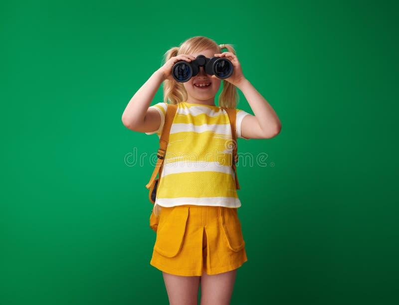 Uśmiechnięta szkolna dziewczyna patrzeje przez lornetek obrazy royalty free
