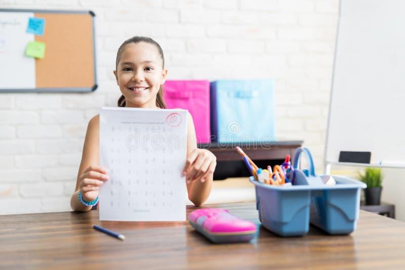 Uśmiechnięta Szkolna dziewczyna Pokazuje Perfect wynika testu Przy stołem zdjęcie stock