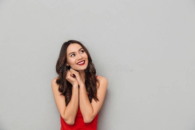 Uśmiechnięta tajemnicy brunetki kobieta w przypadkowych ubrań przyglądający up zdjęcie royalty free