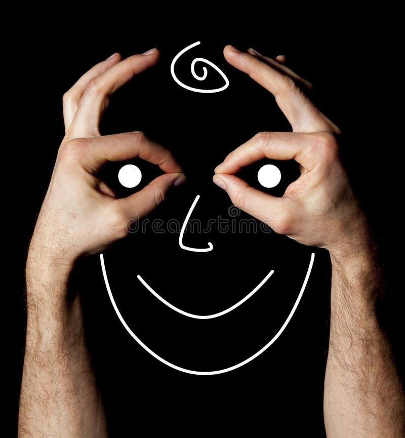 Uśmiechnięta twarz między dwa pokazuje szyldowymi ok rękami zdjęcie stock
