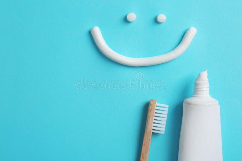Uśmiechnięta twarz robić pasta do zębów, tubka, muśnięcie i przestrzeń dla teksta, na koloru tle zdjęcie stock