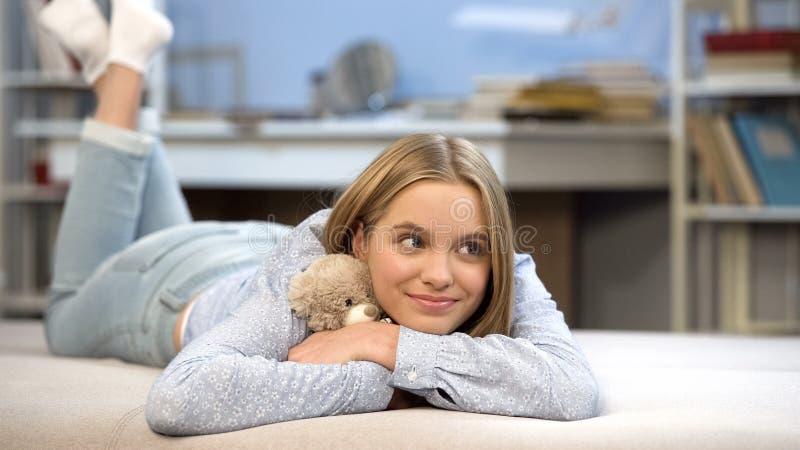 Uśmiechnięta uczennica ściska jej miś zabawkę w sypialni, dzieciństwo domu wygoda fotografia stock