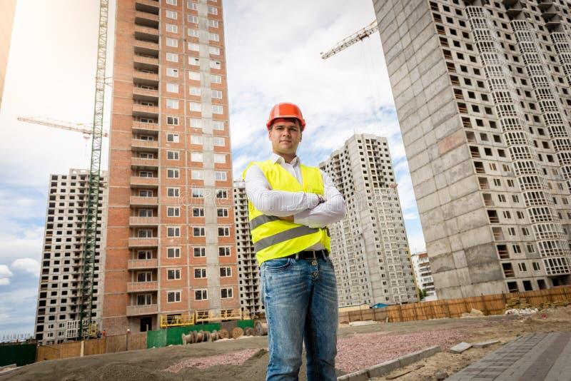 Uśmiechnięta ufna architekt pozycja przy budynkami pod construc zdjęcia royalty free
