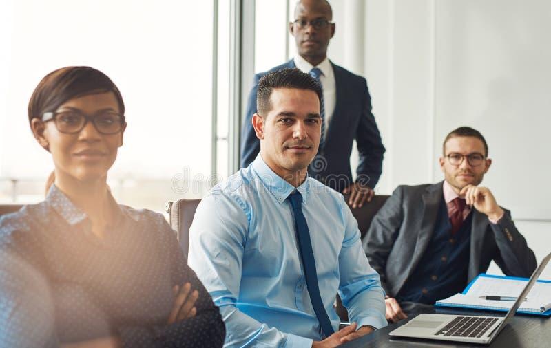 Uśmiechnięta ufna biznes drużyna sadzająca przy stołem obrazy stock