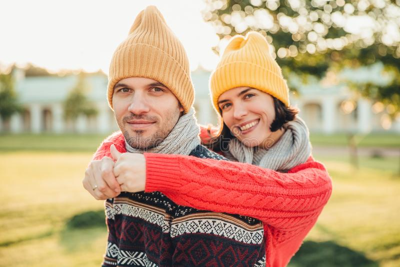 Uśmiechnięta uradowana młoda kobieta w kapeluszu i ciepłym bawełnianym pulowerze obejmuje jej męża który stoi z powrotem, cieszy  obraz royalty free