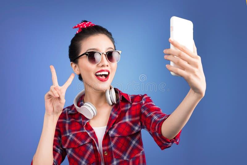 Uśmiechnięta urocza aktywna azjatykcia dziewczyna bierze selfie fotografię zdjęcie stock