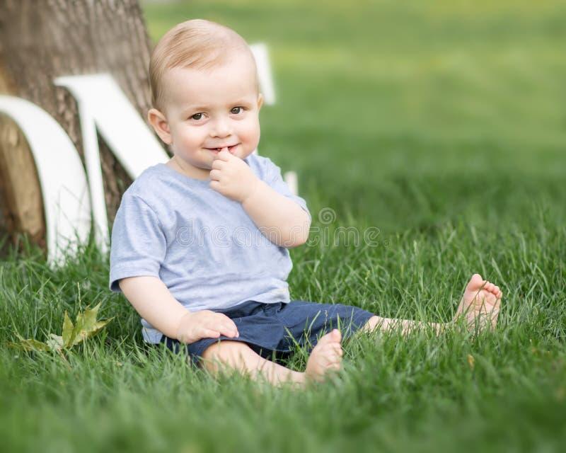 Uśmiechnięta urocza mała chłopiec trzyma palec plenerowy przy lato parkiem w jego usta obsiadaniu na zielonej trawie Emocje, uśmi zdjęcie royalty free