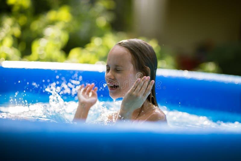 Uśmiechnięta urocza siedem lat dziewczyna bawić się zabawę i ma w nadmuchiwanym basenie obraz royalty free
