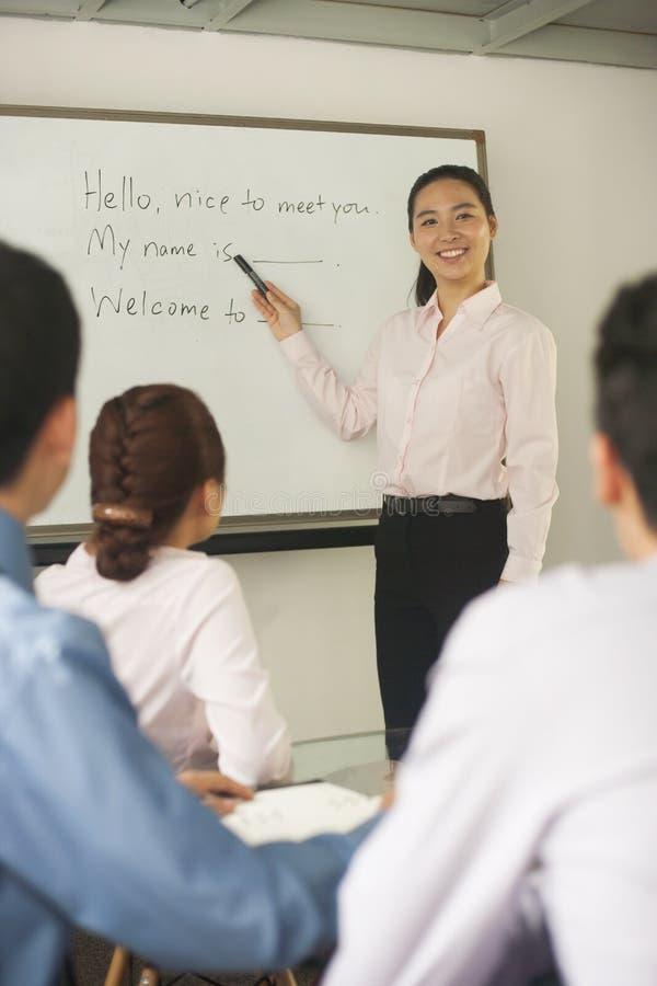 Uśmiechnięta urzędnik pozycja przy whiteboard i nauczania coworkers fotografia royalty free