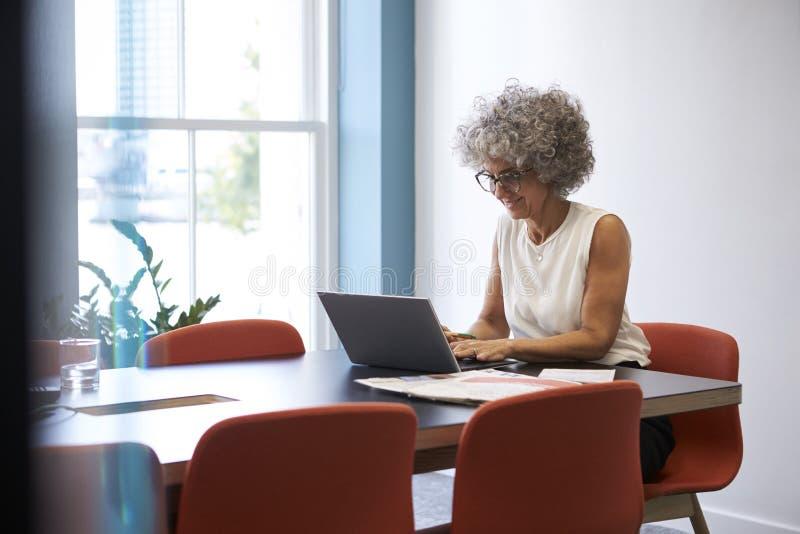 Uśmiechnięta w średnim wieku kobieta pracuje samotnie w biurowej sala posiedzeń fotografia stock