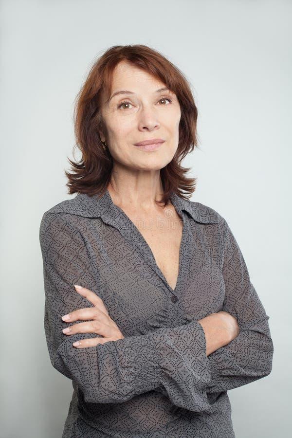 Uśmiechnięta w połowie dorosła biznesowa kobieta z krzyżować rękami na bielu fotografia stock