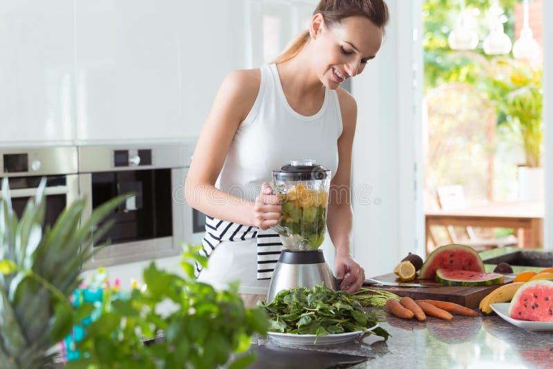 Uśmiechnięta weganin kobieta robi smoothie obrazy stock