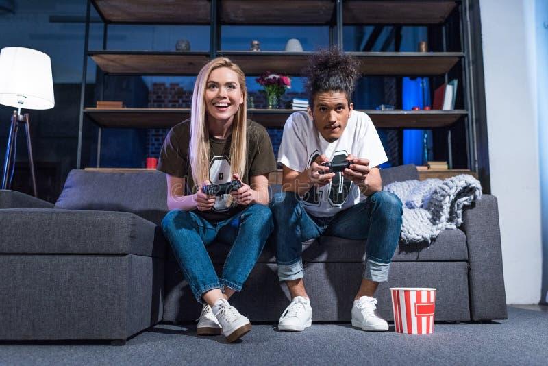 uśmiechnięta wieloetniczna para bawić się wideo grę wpólnie zdjęcie royalty free