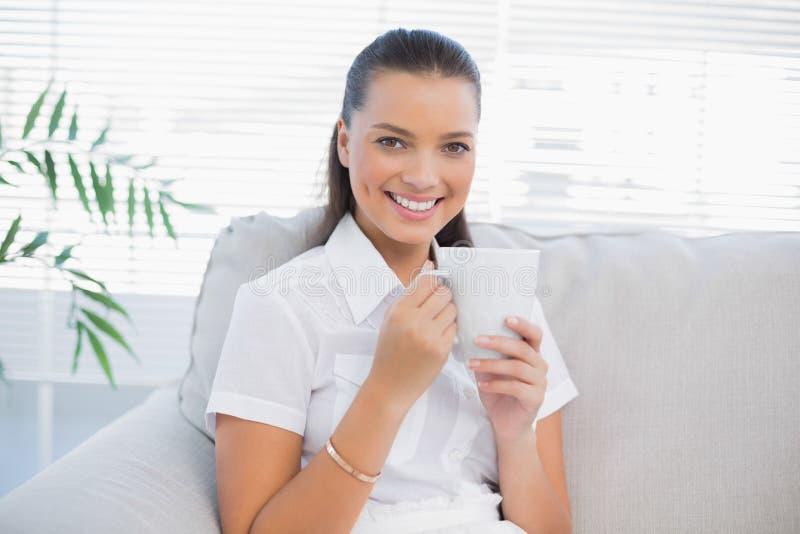 Uśmiechnięta wspaniała kobieta trzyma gorącą kawę fotografia stock