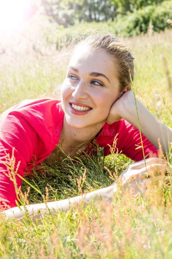 Uśmiechnięta wspaniała młoda kobieta relaksuje w trawie, oddycha wellbeing zdjęcie stock