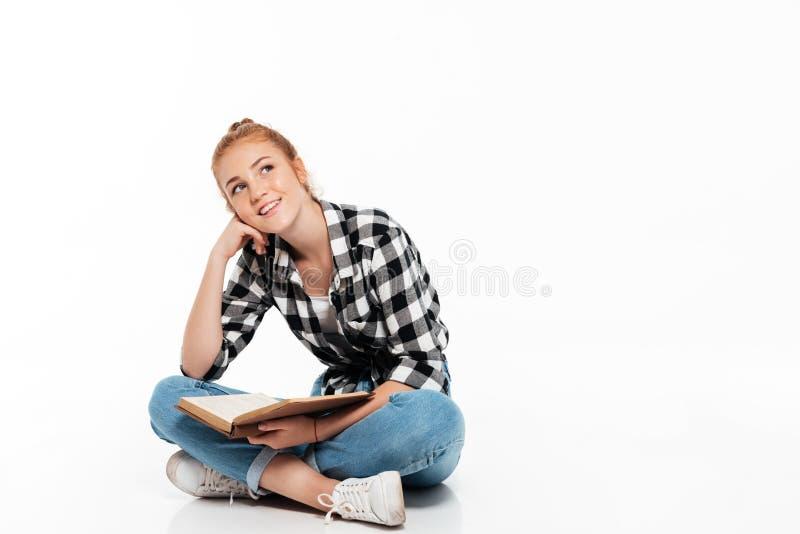Uśmiechnięta zadumana imbirowa kobieta w koszulowym obsiadaniu na podłoga fotografia royalty free