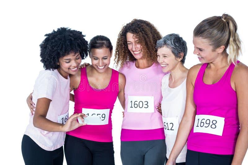 Uśmiechnięte żeńskie atlety używa smartphone zdjęcia stock