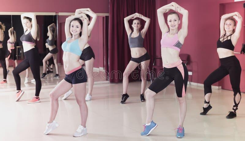 Uśmiechnięte aktywne kobiety ćwiczy tanów ruchy zdjęcia stock