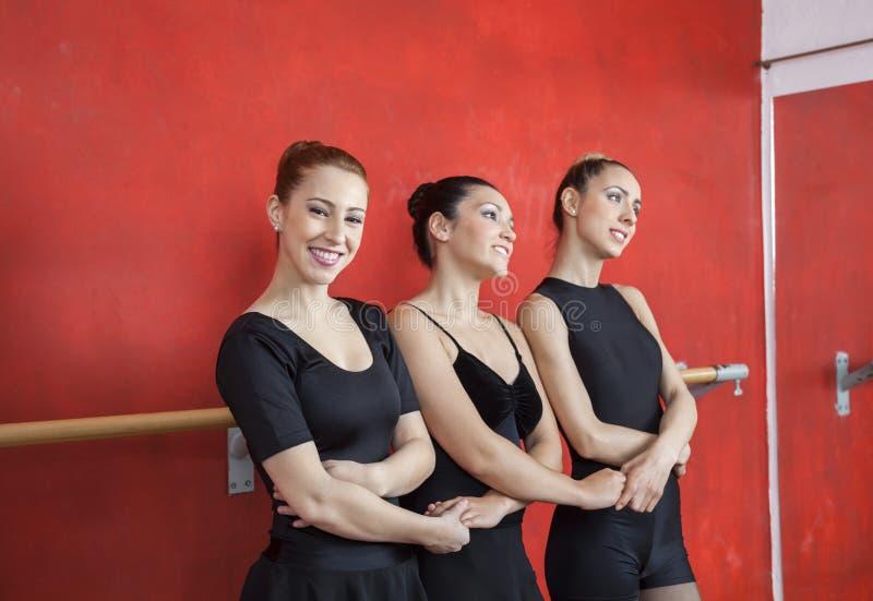 Uśmiechnięte baleriny mienia przyjaciół ręki W studiu fotografia stock