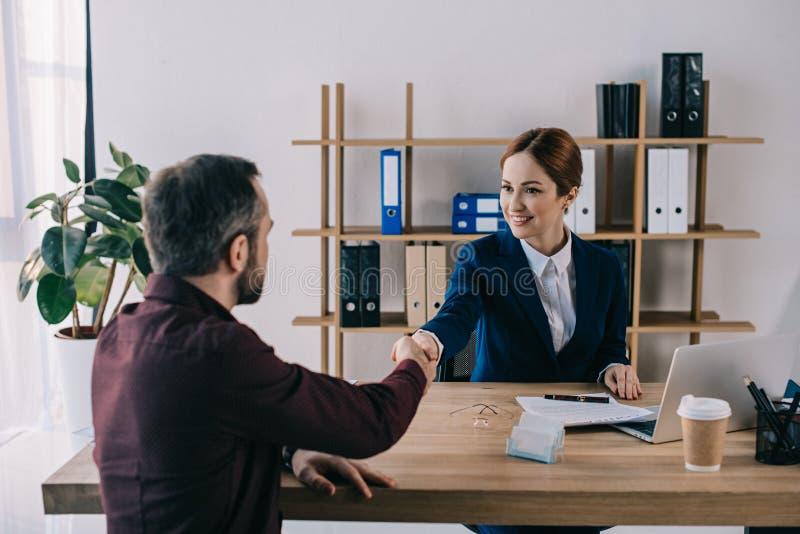 uśmiechnięte bizneswomanu i klienta chwiania ręki na spotkaniu zdjęcie royalty free