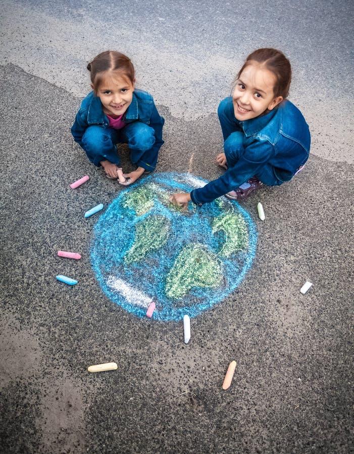 Uśmiechnięte dziewczyny rysuje ziemię z piszą kredą na ulicie obraz royalty free