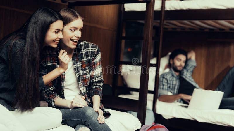 Uśmiechnięte dziewczyny siedzą na łóżkowym i patrzeje facecie zdjęcia royalty free