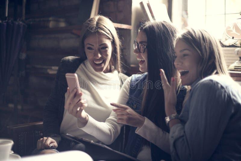 Uśmiechnięte dziewczyny używa mądrze telefon zdjęcie royalty free