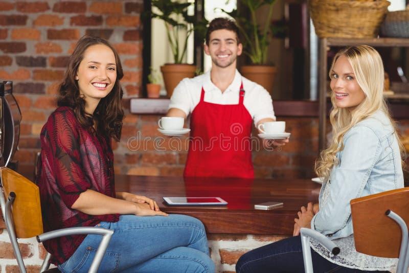 Uśmiechnięte kelner porci kawy klienci zdjęcia royalty free