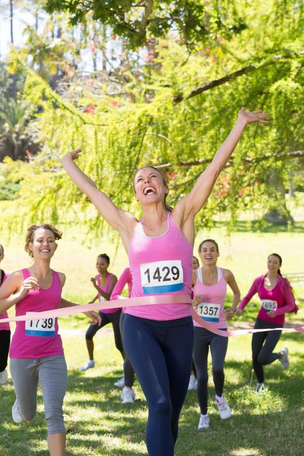 Uśmiechnięte kobiety biega dla nowotwór piersi świadomości obrazy stock
