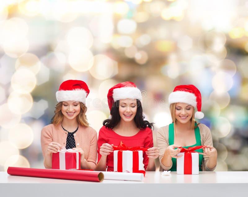 Uśmiechnięte kobiety pakuje prezenty w Santa pomagiera kapeluszach zdjęcie royalty free