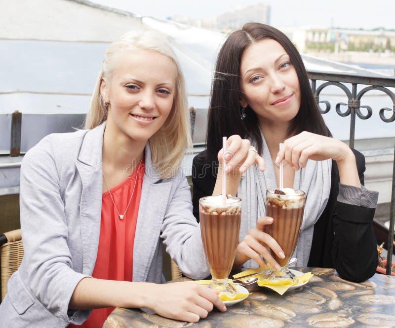 Uśmiechnięte kobiety pije kawowego siedzącego outside w cukiernianym bistrze obrazy royalty free