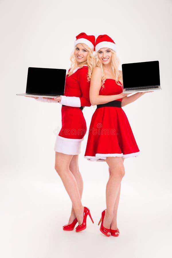 Uśmiechnięte kobiety w Santa laptopu sukiennym pokazuje pustym ekranie fotografia stock
