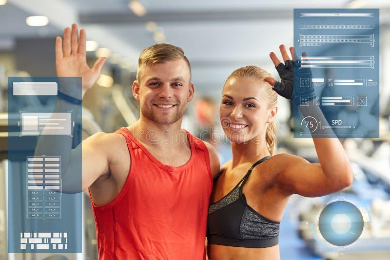 Uśmiechnięte mężczyzna i kobiety falowania ręki w gym zdjęcia stock