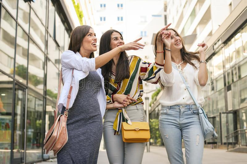 Uśmiechnięte młode dziewczyny chodzi na ulicie z torba na zakupy dziewczyna s fotografia stock