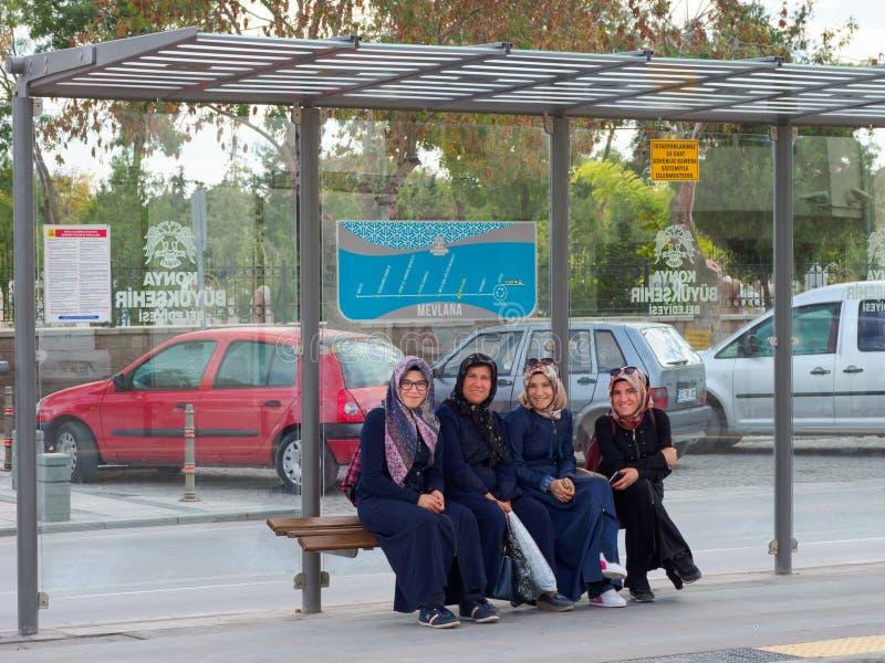 Uśmiechnięte Muzułmańskie kobiety siedzi przy tramwajową przerwą w Konya mieście, Trukey obrazy stock