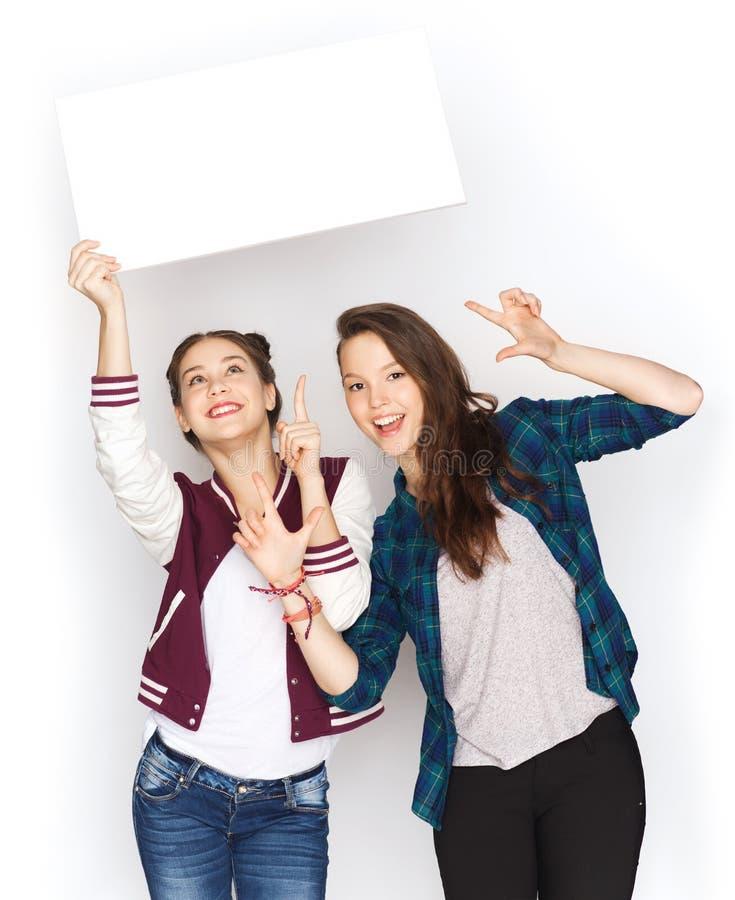 Uśmiechnięte nastoletnie dziewczyny trzyma białą puste miejsce deskę zdjęcie stock
