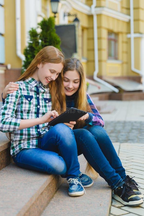 Uśmiechnięte nastoletnie dziewczyny z pastylka komputeru osobistego komputerem outdoors obrazy stock