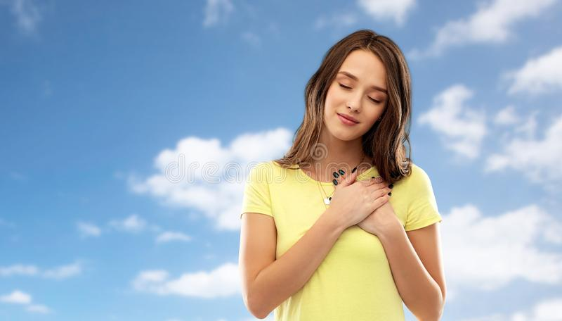 Uśmiechnięte nastoletniej dziewczyny mienia ręki na sercu obrazy royalty free