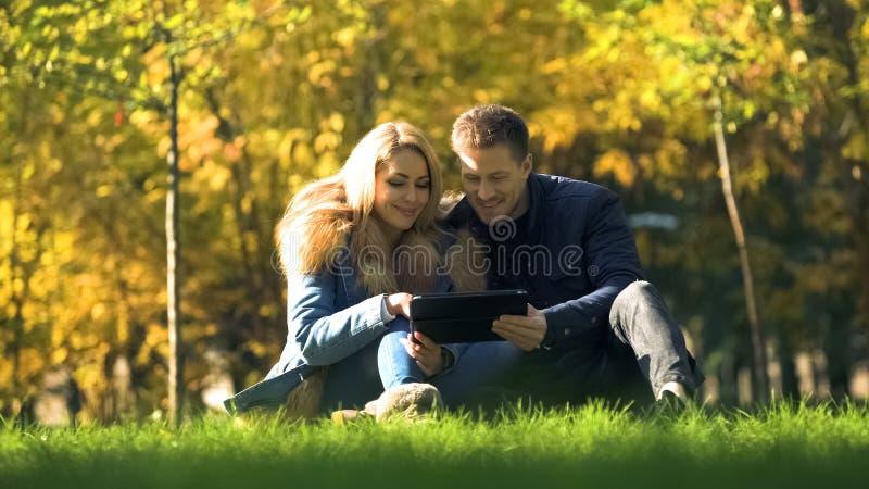 Uśmiechnięte pary dopatrywania fotografie na pastylce, siedzi w pięknym jesień parku fotografia stock