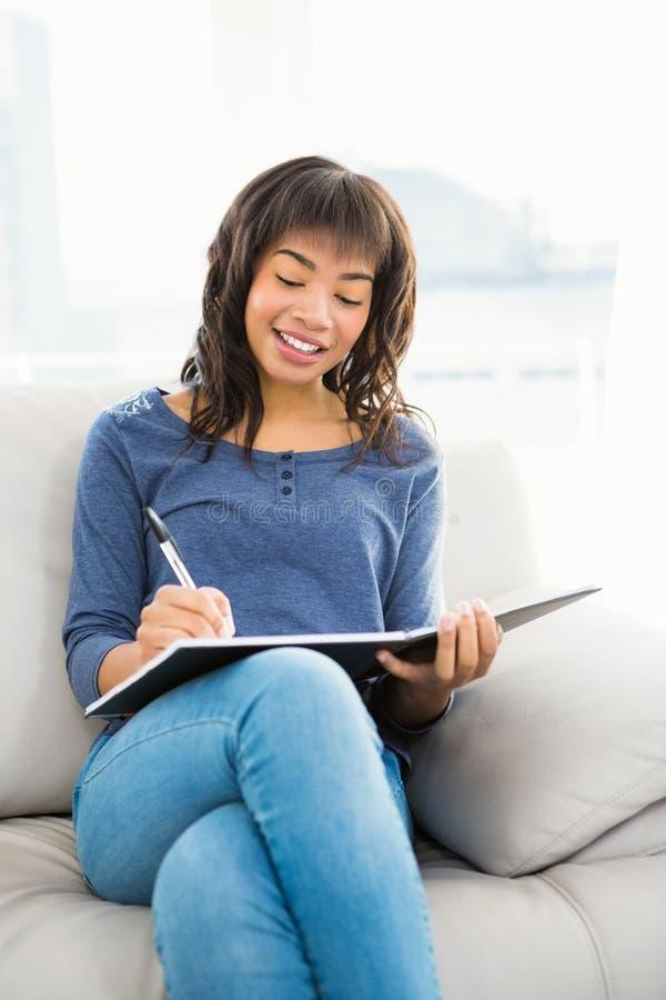 Uśmiechnięte przypadkowe kobiety writing notatki obraz royalty free
