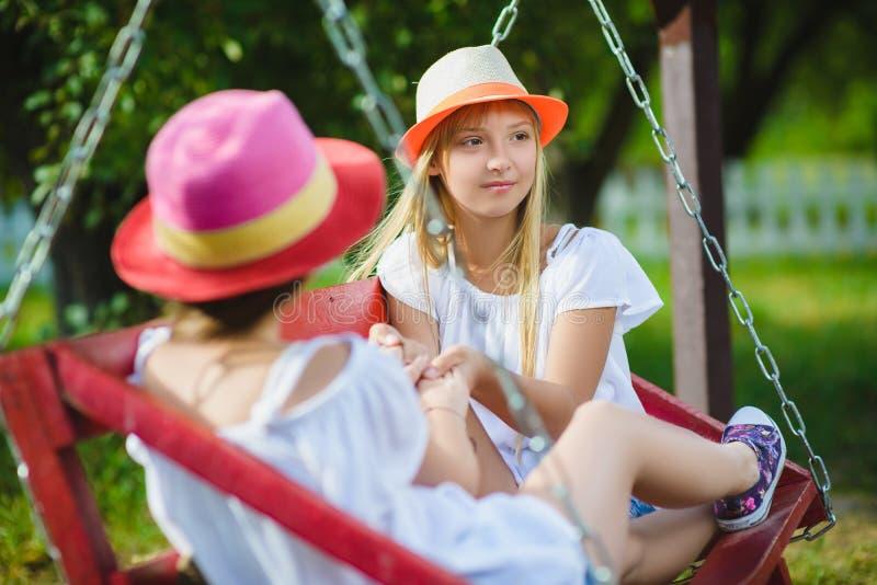 Uśmiechnięte szczęśliwe nastoletnie caucasian dziewczyny na huśtawce zdjęcie royalty free