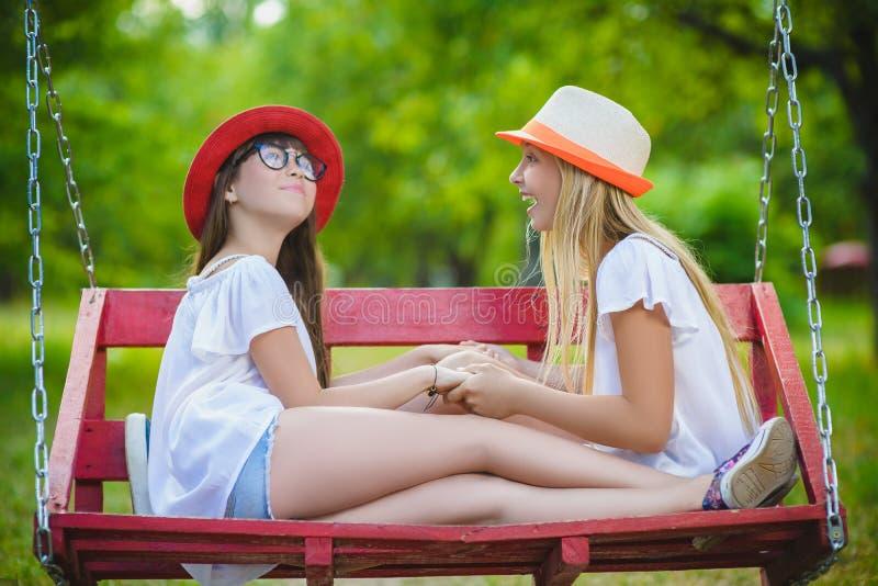 Uśmiechnięte szczęśliwe nastoletnie caucasian dziewczyny na huśtawce obraz royalty free