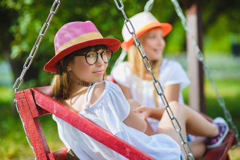 Uśmiechnięte szczęśliwe nastoletnie caucasian dziewczyny na huśtawce obrazy stock
