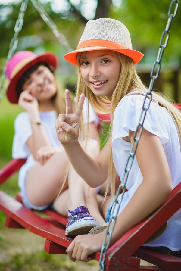 Uśmiechnięte szczęśliwe nastoletnie caucasian dziewczyny na huśtawce obraz stock