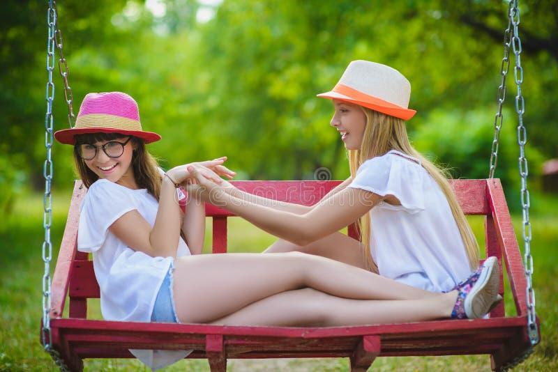 Uśmiechnięte szczęśliwe nastoletnie caucasian dziewczyny na huśtawce fotografia royalty free