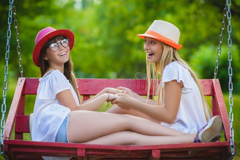 Uśmiechnięte szczęśliwe nastoletnie caucasian dziewczyny na huśtawce obrazy royalty free