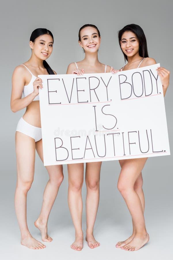 uśmiechnięte wielokulturowe kobiety trzyma sztandar z pisać list każdy ciało są piękne zdjęcie stock